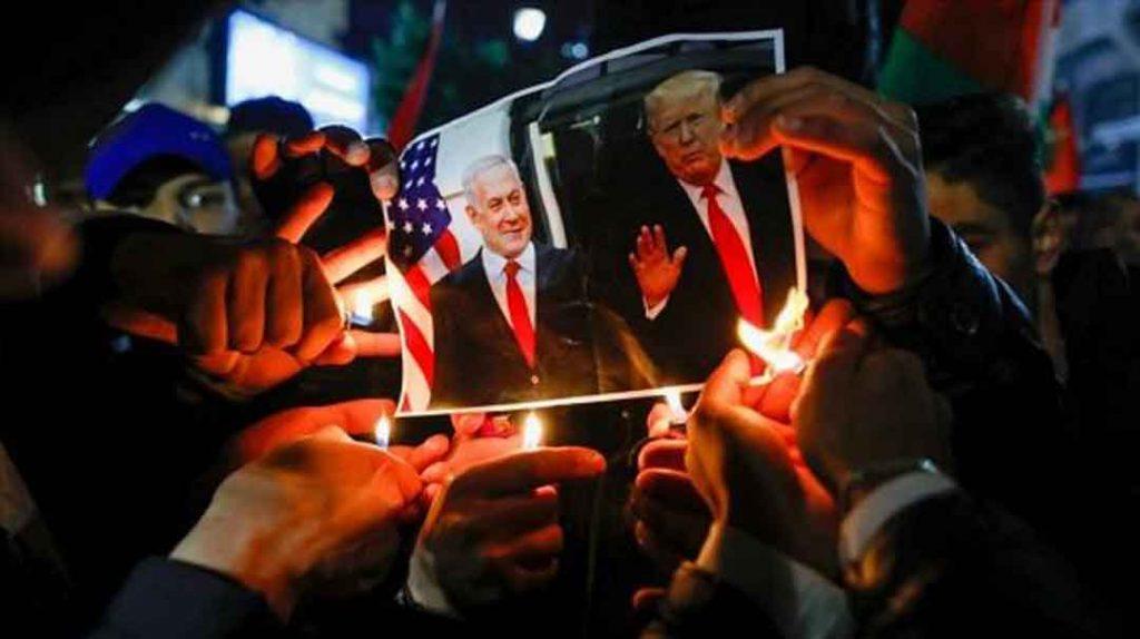 Manifestantes palestinos queman una foto del presidente de EE.UU. y el premier israelí en Ramalá, 28 de enero de 2020. Foto: AFP.